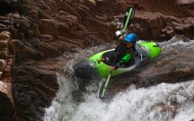 Woman kayaking at the edge of a waterfall