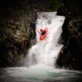 Woman kayaking down a waterfall