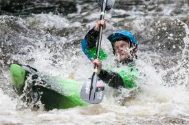 Woman being splashed while kayaking