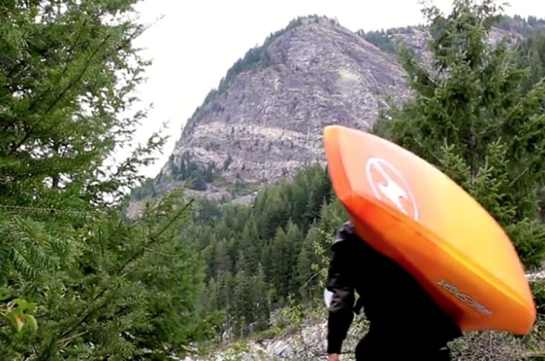 kayaker carrying kayak through the wilderness