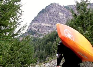 kayaker carrying kayak through the wilderness